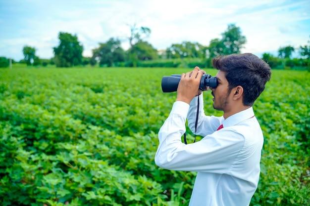 インドの男性は双眼鏡で自然の中で楽しんでいます Premium写真