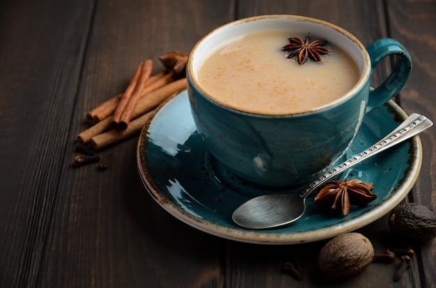 Indian masala chai tea. spiced tea with milk on dark  wooden. Premium Photo
