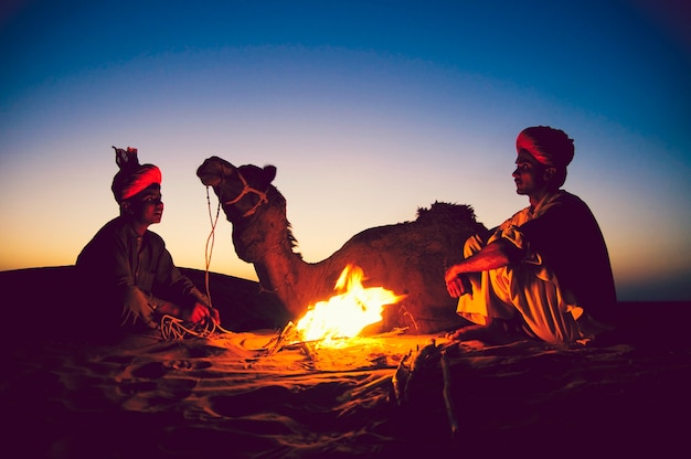 Indian men resting by the bonfire with their camel Premium Photo