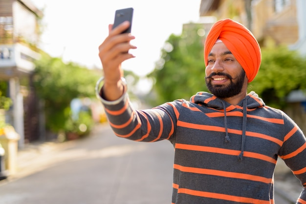 Indian sikh man wearing turban and taking selfie with phone Premium Photo