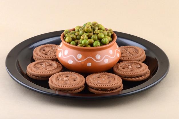インドのおやつ:プレートにクリームビスケットとスパイスで揚げたグリーンピース(チャタパマタル)。 Premium写真