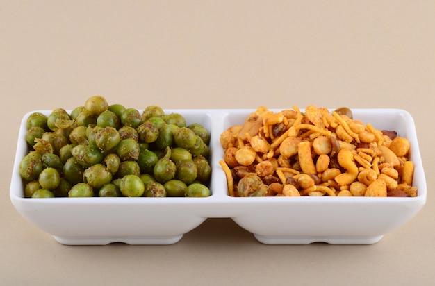 インドのスナック:白い皿にミックスとスパイスで揚げたグリーンピース(chatpata matar)。 Premium写真