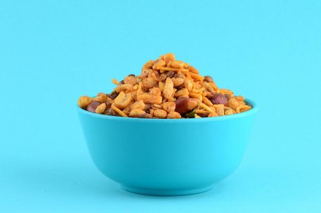 インドのスナック:青のボウルでの混合物(塩コショウマサラ、豆、チャンナマサラダルグリーンピースのローストナッツ) Premium写真