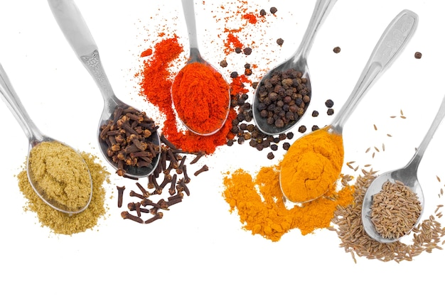 Indian spices in spoons isolated on white background Premium Photo