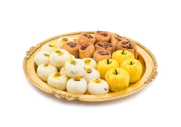 Indian spicy bhakarwadi with apple shaped peda or white peda Premium Photo