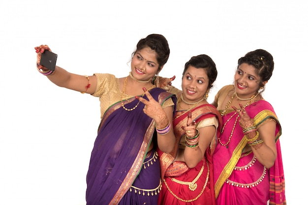 Indian traditional girls taking selfie with smartphone on white surface Premium Photo