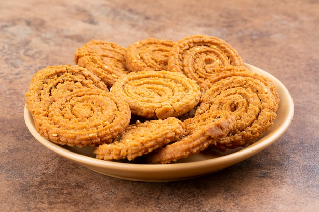 Indian traditional snack chakli, a spiral shaped crisp deep fried snack Premium Photo