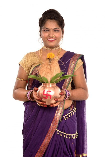 Indian traditional woman holding a traditional copper kalash, indian festival, copper kalash with coconut and mango leaf with floral decoration, essential in hindu puja. Premium Photo