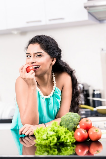 Indian woman eating healthy apple in her kitchen Premium Photo