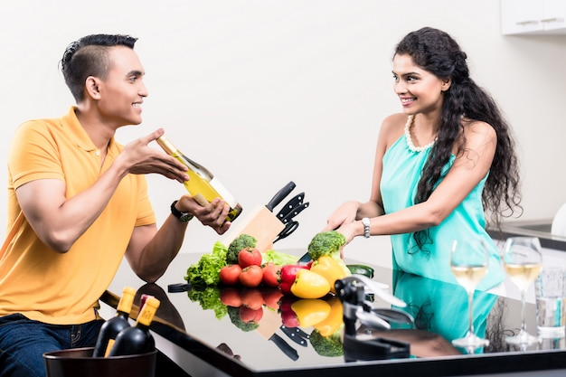 Indian woman and man in kitchen with red wine Premium Photo