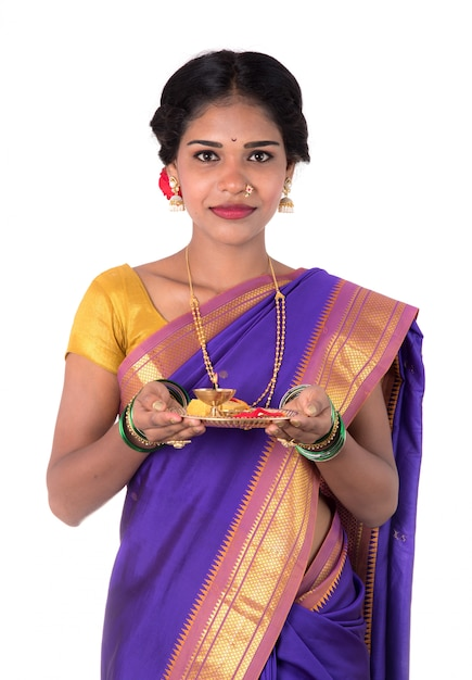 Indian woman performing worship, portrait of a beautiful young lady with pooja thali isolated on white wall Premium Photo