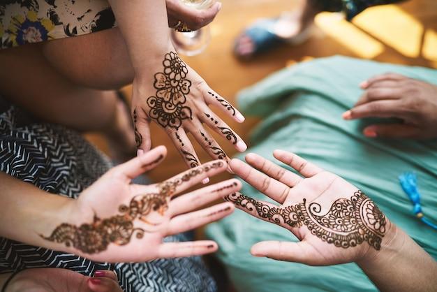 Indian women showing hand with henna tattoo art (mehndi) Premium Photo