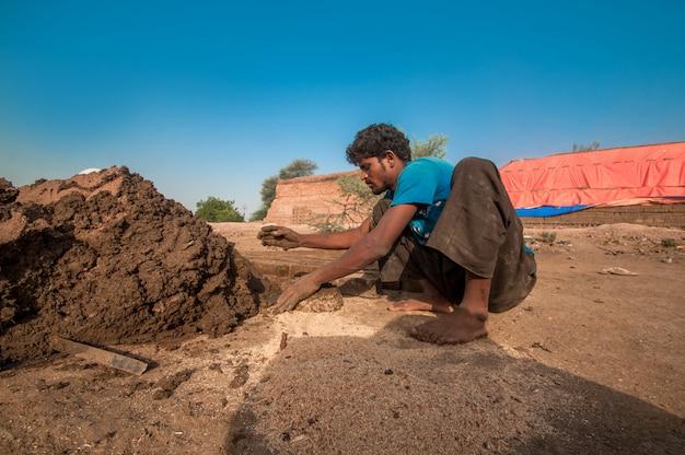 レンガ工場で手作業で伝統的なレンガを作るインドの労働者 Premium写真
