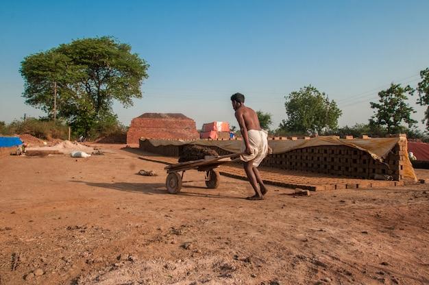 レンガ工場で粘土を処理して運ぶインドの労働者 Premium写真