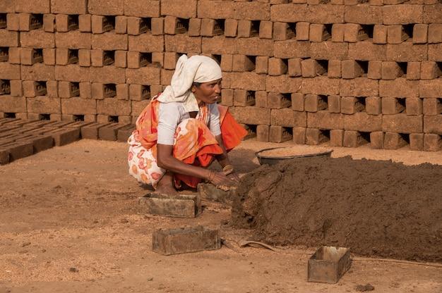インドの労働者が粘土または泥で処理し、レンガ窯または工場またはフィールドで手作業で伝統的なレンガを作ります。 Premium写真