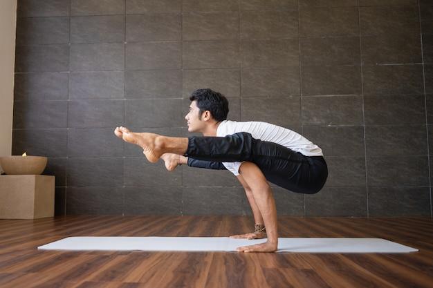 Indian yogi doing firefly yoga pose in gym Free Photo