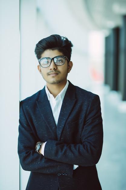 近代的なオフィスに立っているインドの青年実業家 無料写真