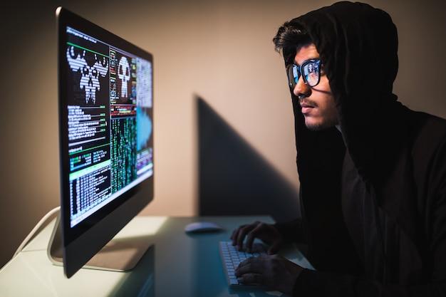 Pirata informatico di indianmale con lo smartphone e codifica sullo schermo di computer nella stanza scura Foto Gratuite