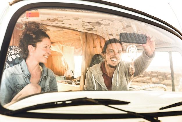 Indie couple ready for roadtrip on oldtimer mini van transport Premium Photo