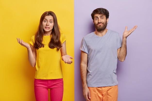 Indifferent unbothered woman and man spread hands sideways Free Photo