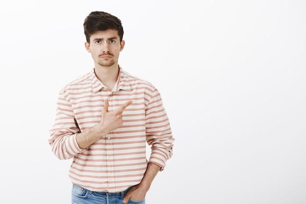 ひげと口ひげを持つ無関心で興味のない白人男性モデル、ポケットに手を握って、憂鬱な顔で右上隅を指す 無料写真