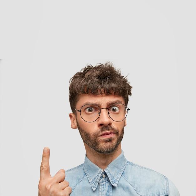 Возмущенный бородатый мужчина смотрит сердито, с недовольным выражением лица, показывает указательным пальцем вверх Бесплатные Фотографии
