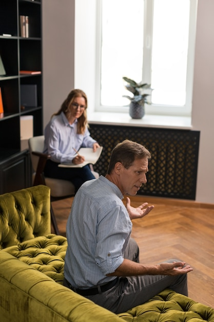 話したりジェスチャーをしたりしながらソファに座っている憤慨した茶色の髪の青い目の男 Premium写真