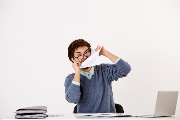 Возмущенный бизнесмен рвет бумагу, кусает документы, сходит с ума, садится за рабочий стол, испытывает эмоциональный выгорание Бесплатные Фотографии