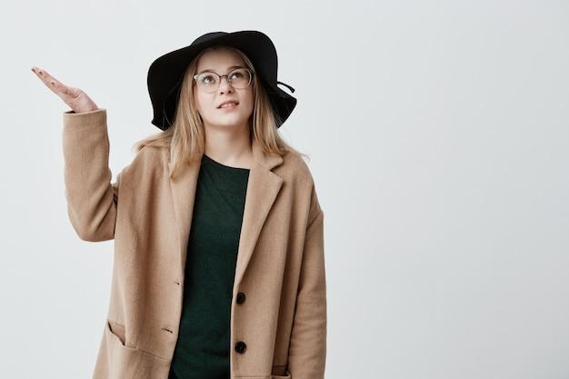 La studentessa indignata gesticola con indignazione in cappotto e cappello nero, sta in strada, non sa cosa fare a causa del maltempo. ragazza bionda dispiaciuta e insoddisfatta che è perplessa Foto Gratuite