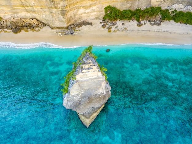 インドネシア。ペニダ島の崖の近くの空のビーチ。海岸近くの鋭い岩。航空写真 Premium写真