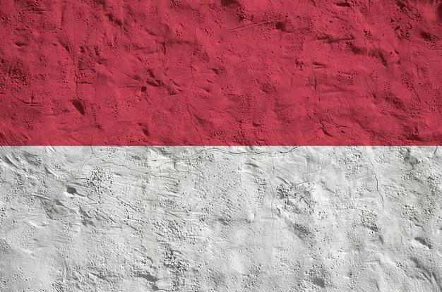 Флаг индонезии изображен яркими красками на старой рельефной штукатурке стены. Premium Фотографии