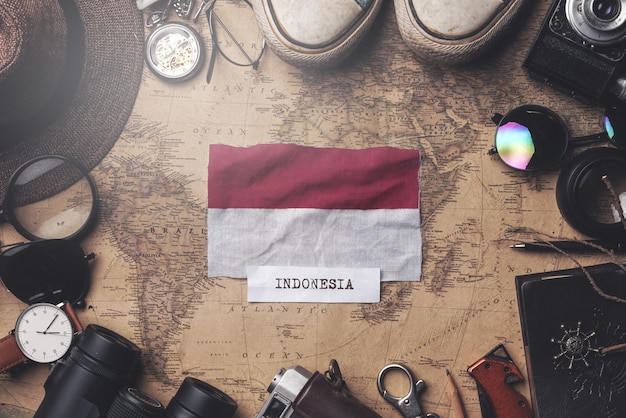 Indonesia flag between traveler's accessories on old vintage map. overhead shot Premium Photo
