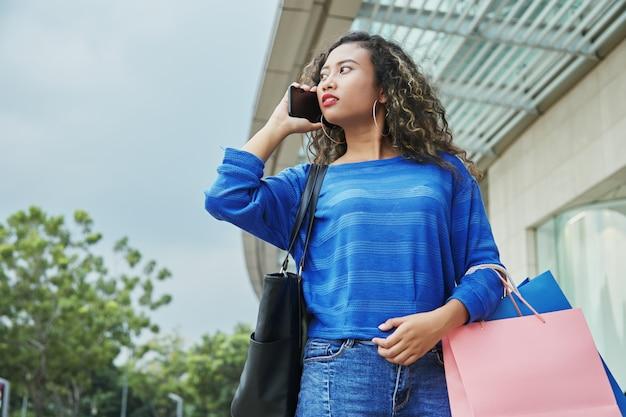 Индонезийская женщина разговаривает по телефону во время покупок Бесплатные Фотографии