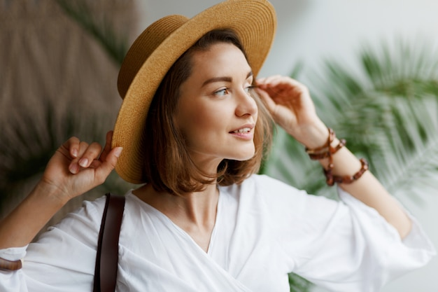 麦わら帽子と白いブラウスを自宅でポーズでエレガントなきれいな女性の肖像画間近で屋内 無料写真