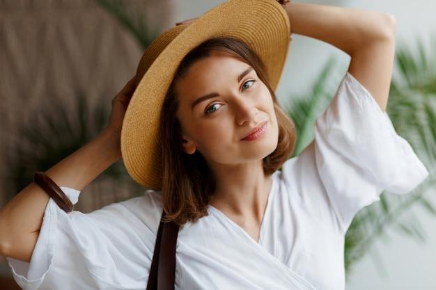 麦わら帽子と白いドレスが自宅でポーズでエレガントなきれいな女性の肖像画間近で屋内 無料写真