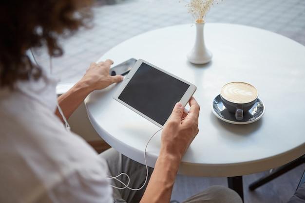 카페 테이블 위에 남자의 손의 실내 확대 측면보기, 이어폰으로 태블릿을 들고 스마트 폰에 도달하고 커피 한잔 할 것입니다. 무료 사진