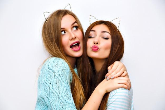Внутренний модный портрет образа жизни довольно счастливых друзей-женщин, объятий, одетых в уютные пастельные кашемировые мятные свитера, брюнетки и светлых волос, макияжа, модного аксессуара, посылающего воздушный поцелуй. Бесплатные Фотографии