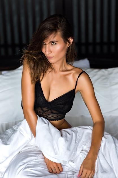Ritratto di moda al coperto di donna bruna sexy che indossa reggiseno di pizzo nero e rilassarsi nel suo cattivo stile di vita di lusso, bellezza naturale, tempo del mattino. Foto Gratuite