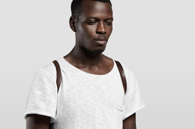 Выстрел в голову симпатичного темнокожего студента, одетого в белую пустую футболку и кожаный рюкзак, стоящего изолированно у бетонной стены Бесплатные Фотографии