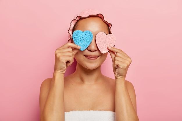 Горизонтальный снимок восхищенной молодой азиатской женщины в помещении прикрывает глаза двумя губками в форме сердца, развлекается после душа, пользуется косметическими средствами для нанесения крема, у нее темная гладкая кожа. Бесплатные Фотографии