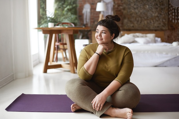 Indoor image of charming positive overweight young caucasian female in sportswear relaxing on floor, sitting on yoga mat after physical training, having joyful facial expression. looking away Free Photo