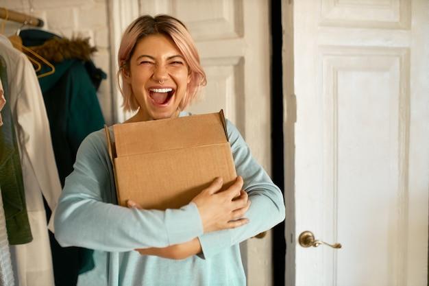 段ボール箱を持ってアパートに届けられ、興奮を表現し、小包を開梱しようとしている幸せな陽気な若い女性の屋内画像 無料写真