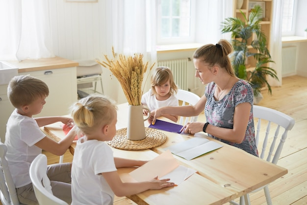 広々としたリビングルームのダイニングテーブルに座って、子供たちに折り紙の作り方を教える若い女性のベビーシッターの屋内画像。家で母親と一緒に紙飛行機を作る3人の子供。 無料写真