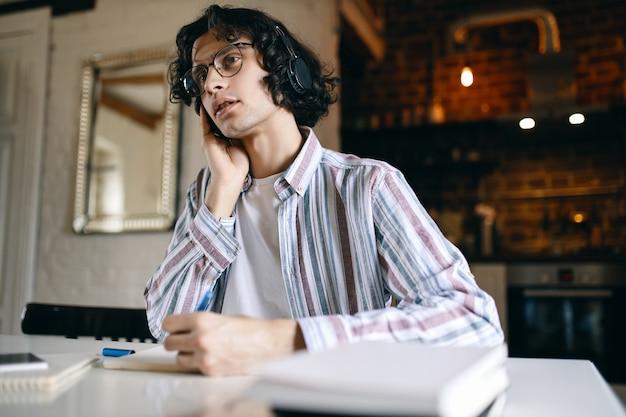 Immagine interna di giovane maschio serio con capelli ricci seduto al suo posto di lavoro con libri di testo, che scrive mentre ascolta la lezione tramite cuffie wireless, imparando da casa. riduzione dei contatti Foto Gratuite