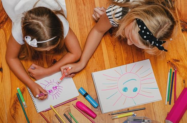 屋内レジャー活動。姉は妹に太陽を引くのを手伝います。上面図。 Premium写真