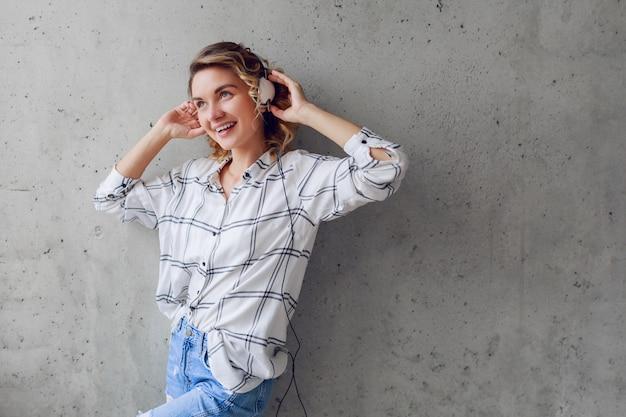 灰色の都市壁の背景に椅子で音楽を聞いて幸せな熱狂的な女性の屋内ライフスタイルの肖像画。 無料写真