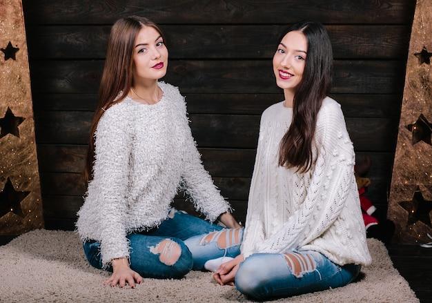 2つのかなり若いおかしい女性の友人の屋内ライフスタイルの肖像画は笑顔と楽しい抱擁 無料写真