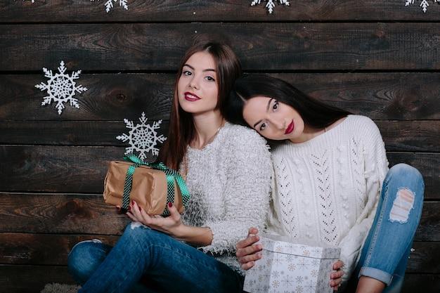 2つのかなり若い面白い女性の友人の屋内ライフスタイルの肖像画は笑顔を抱擁します。 無料写真