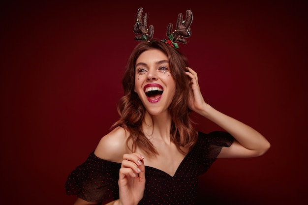 Indoor photo of beautiful joyful young brunette lady with festive hairdo wearing chrismas horns and elegant clothes while posing, expressing true positive emotions Free Photo