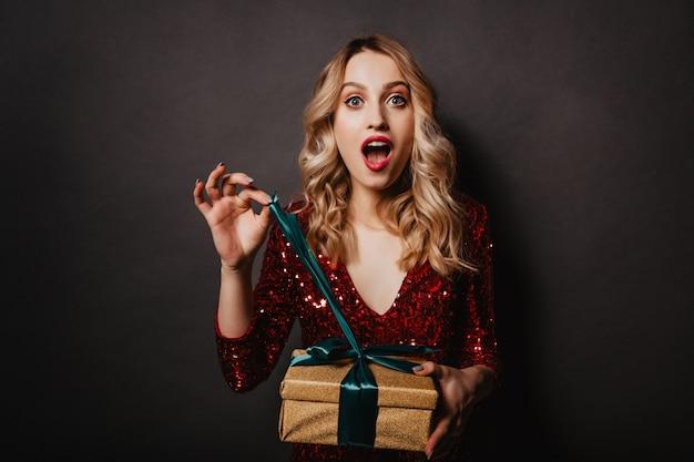 Фотография взволнованной девушки, открывающей подарок в помещении Бесплатные Фотографии